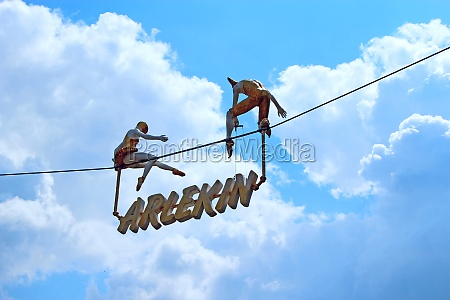 figures of two tightrope walkers and