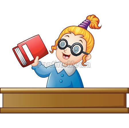 school girl holding textbook at desk