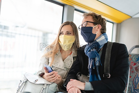 couple in public transport bus wearing