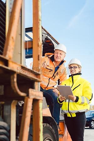 supervisor instructing forklift driver what to