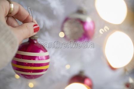 hand decorating christmas tree