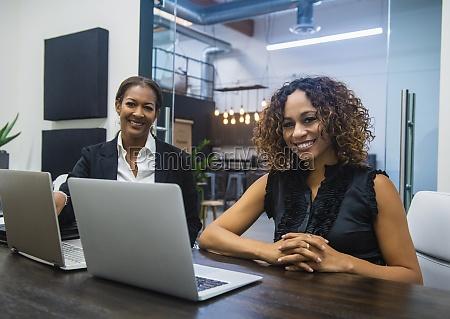 business women using laptops in office