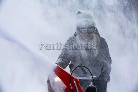 senior woman clearing snow using snowblower