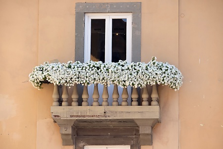 old house with flowers on balcony