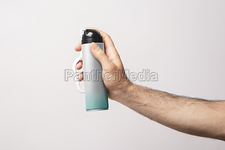 male arm holding a bottle of