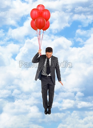businessman flying with red balloons