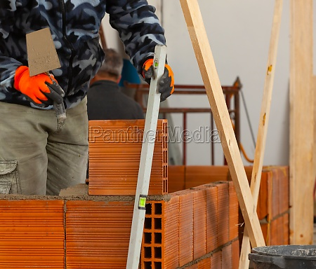 bricklayer installing brick masonry on interior