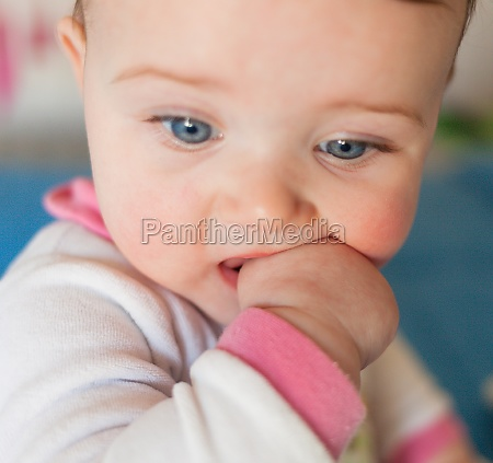 teething concept baby girl with finger