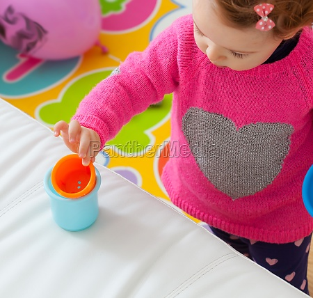 toddler baby girl plays with colored
