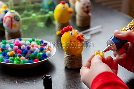 childrens hands apply glue to the
