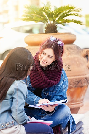 two young women study on a