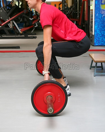 young man doing barbell squats