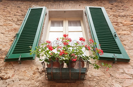 old window with flowers in pienza