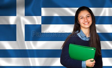 teen student smiling over greek flag
