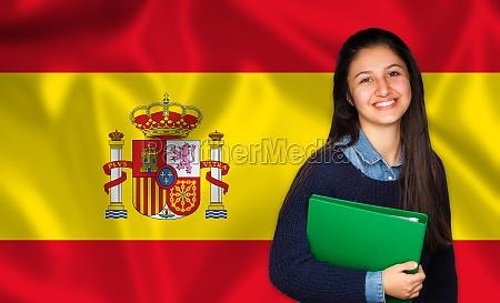 teen student smiling over spanish flag