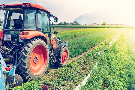 cut out of tractor cultivating field
