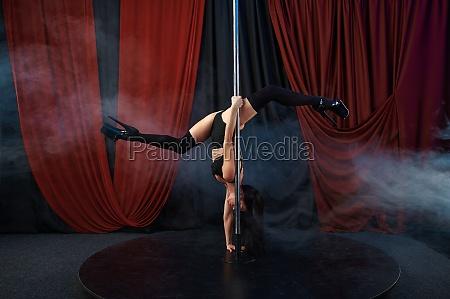 showgirl in black lingerie pole dance