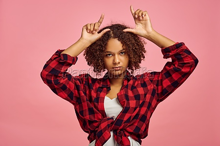 young woman shows horns pink background