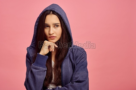 young thoughtful woman in hoodie pink