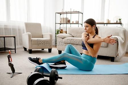 girl sits on floor online fitness