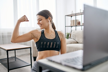woman shows her muscles online fitness