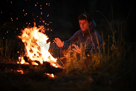 young man making fire while camping