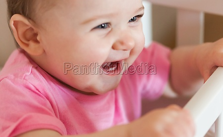 newborn baby girl smiling with two