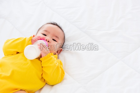 infant holding a bottle of milk