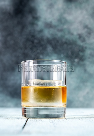 glass of whiskey with ice cube