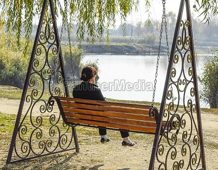 woman is sitting on a swing
