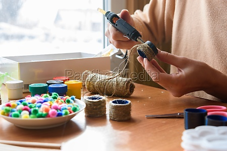 girls hands decorate crafts using twine