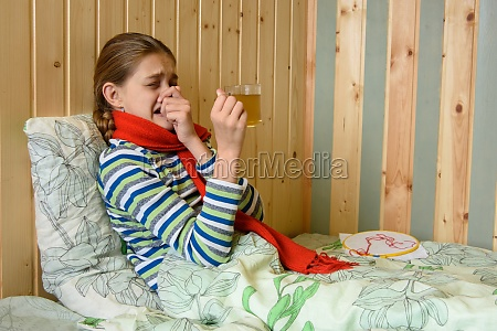 girl sneezes while sitting in bed