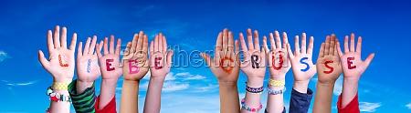 children hands building word liebe gruesse