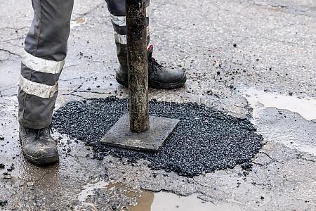 worker pushing bitumen asphalt in the