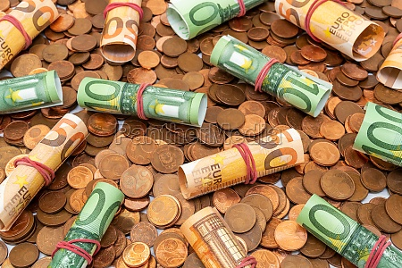 pile of coins with euro banknote