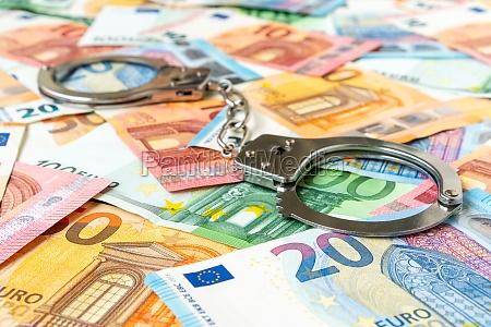 euro banknotes and metal handcuffs