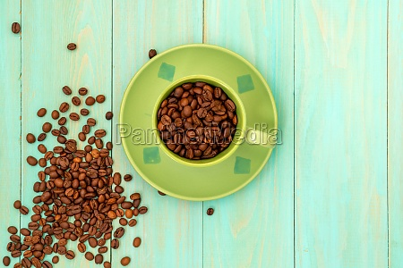 green cup and coffee beans