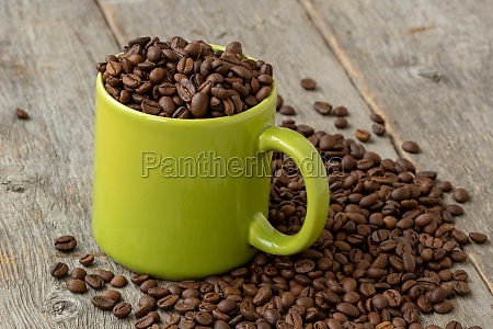 green mug with coffee beans