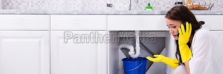 woman calling plumber in front of