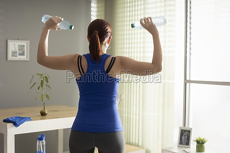 woman doing shoulder exercise with water