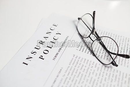 insurance policy contract with spectacles on