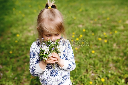 little girl sniffing spring flowers on