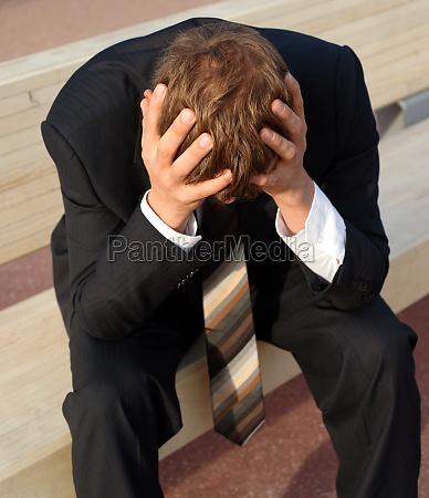 desperate businessman sits sadly on a
