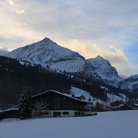 sun lit clouds behind the peaks