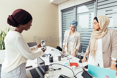 female colleagues discussing robot