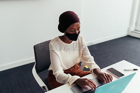 woman working on laptop wearing face