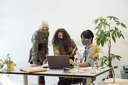 colleagues looking at laptop wearing face