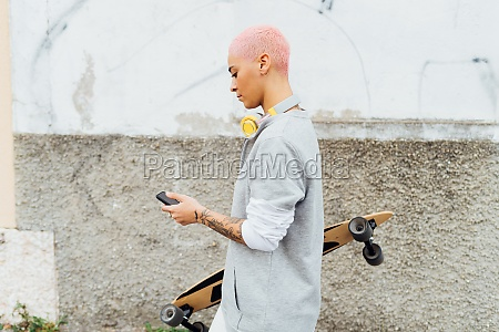 side view of skateboarder using cellphone
