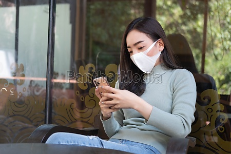 asian female reading text message or