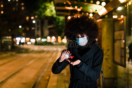 woman using hand sanitizer wearing face